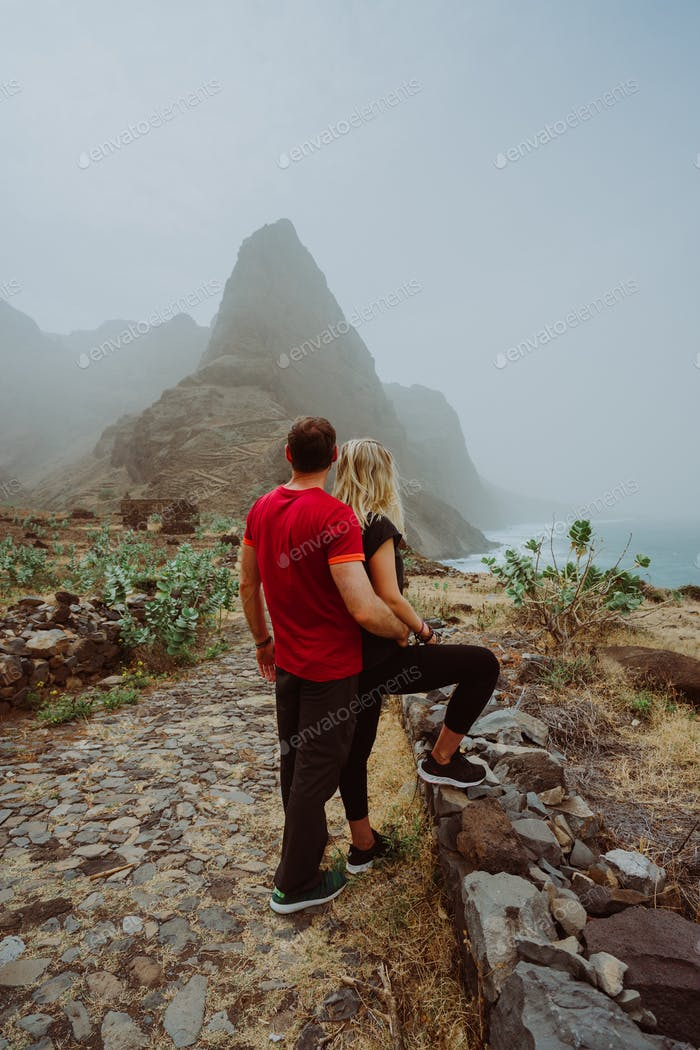 Tourist couple in Aranhas valley hiking from Cruzina to Ponta do Sol. Huge mountains of coastline