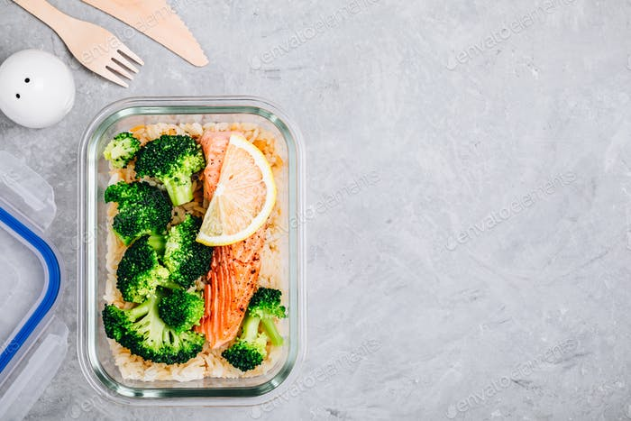 Meal prep lunch box containers with baked salmon fish, rice, green broccoli