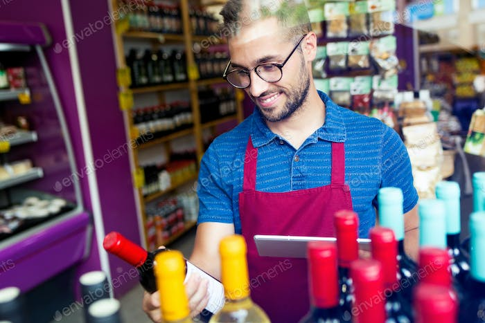 Handsome young salesman selecting a wine bottle in health grocer
