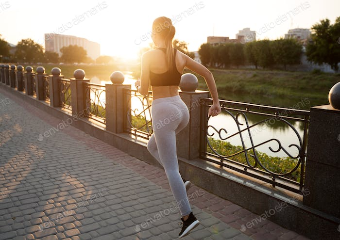 Active sporty woman training on quay, everyday jogging practice