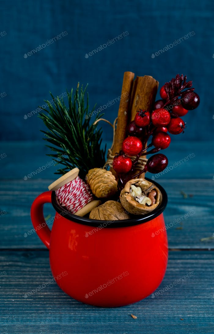 Walnuts, spices and christmas decor in red cup on a blue wood