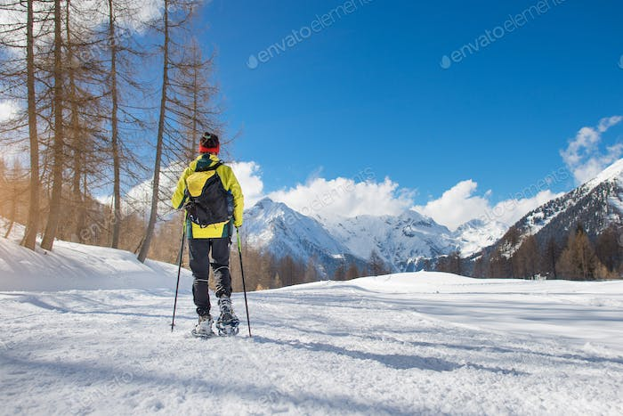 A girl walks with snowshoes