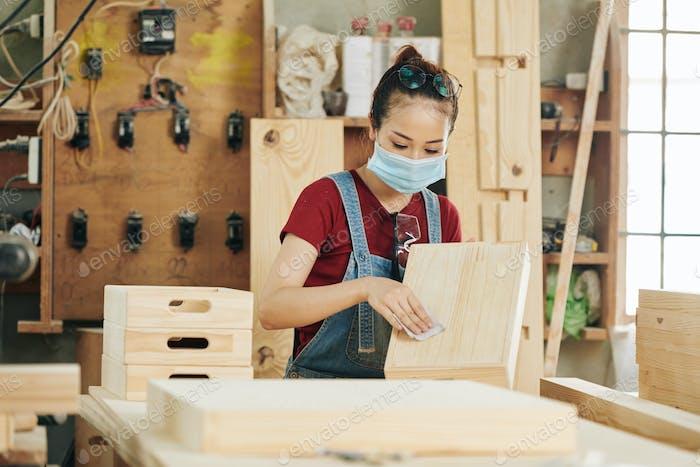 Carpenter sanding wooden drawer