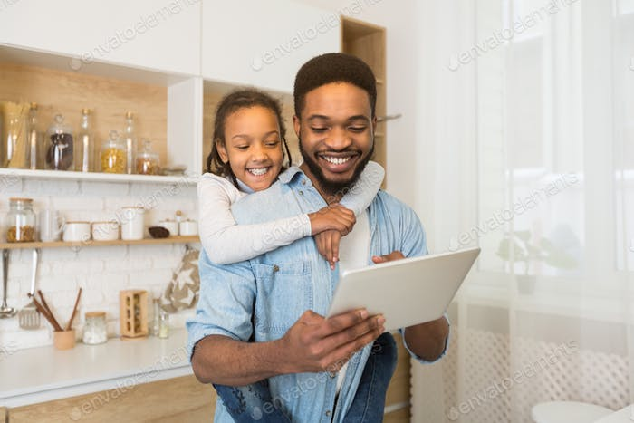 Father and daughter having video call on tablet in kitchen