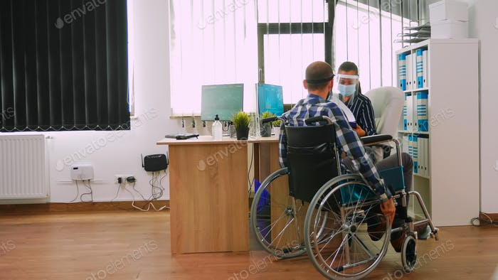 Disabled man keeping distance to prevent covid virus in company