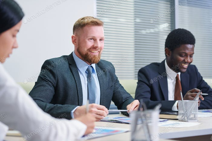 One of two young businessmen talking to partner or colleague