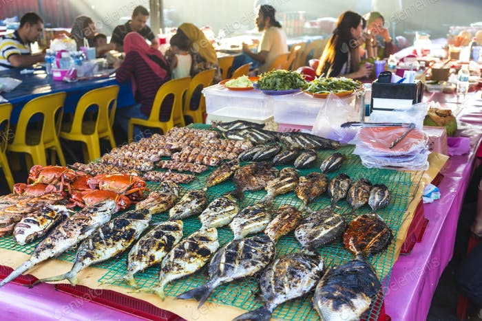 Grilled fish on a table at a food market restaurant