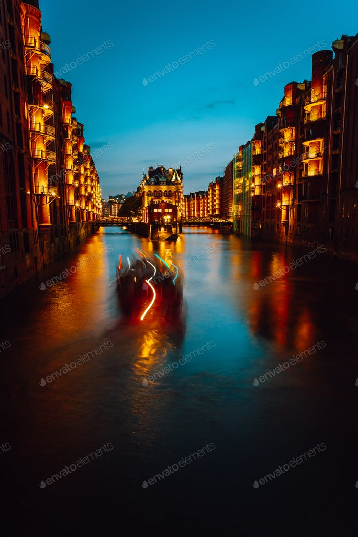 A colorfully illuminated boat cruising on the Wandrahmsfleet at night. The Warehouse District in