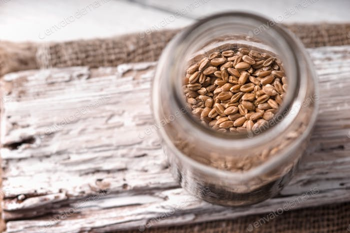 Wheat seeds in a glass jar on a white rustic board side view