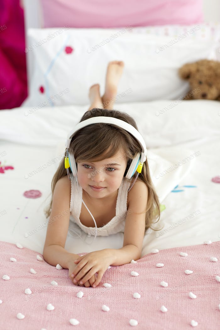 Cute girl listening to the music in bed