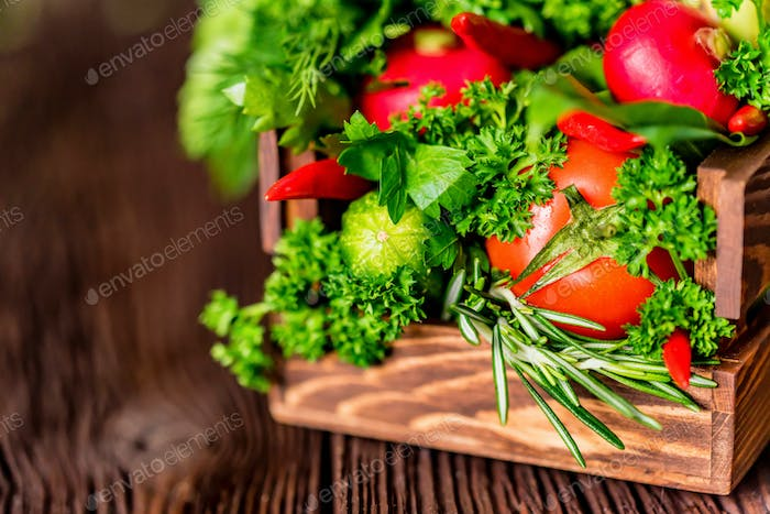 Fresh vegetables and herbs in wooden box