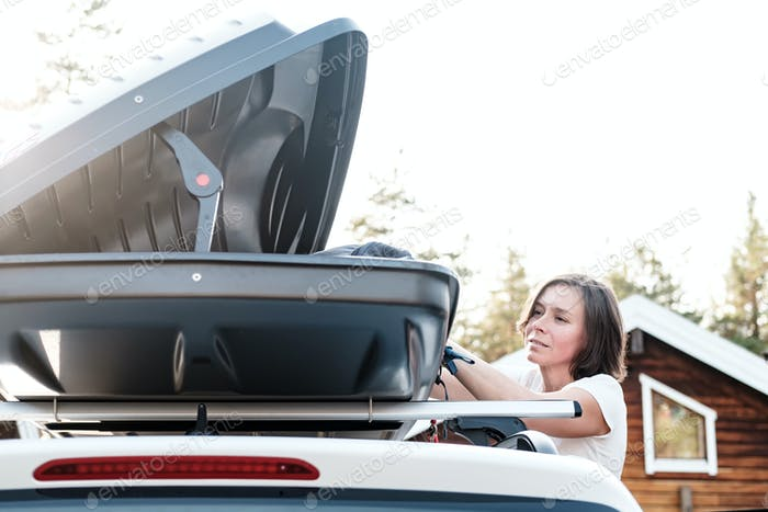 Satisfied woman puts things in the roof rack of the car or in the cargo box