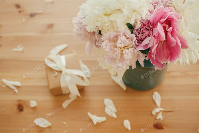 Schöne Pfingstrosen in Vase und Geschenkbox auf rustikalem Holztisch
