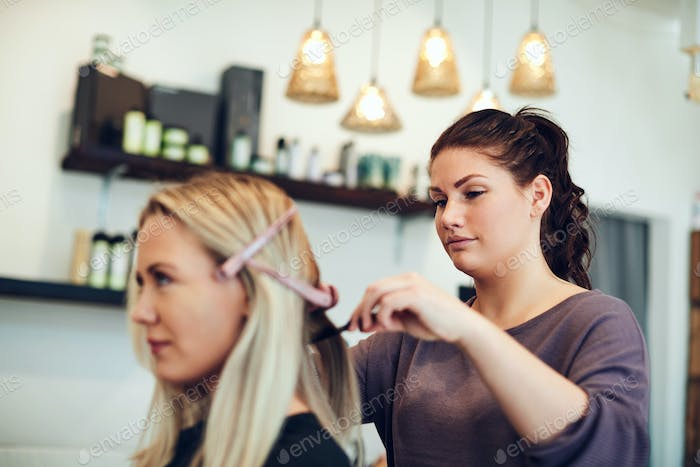 Young hairdresser styling a clients hair in her salon