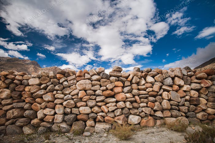 The stone wall under the cloudy sky. Background.
