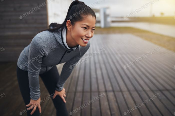 Smiling young Asian woman resting while out jogging