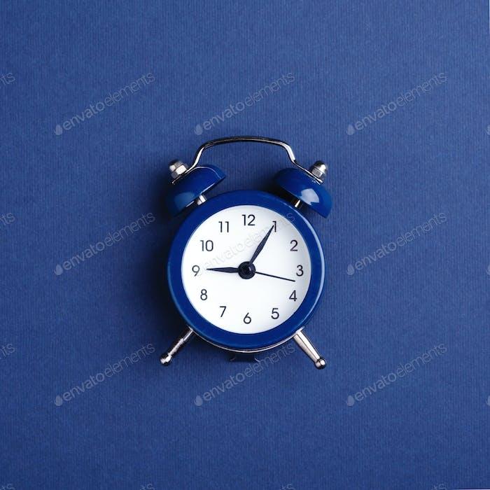 Blue Alarm Clock on Dark Blue Background.