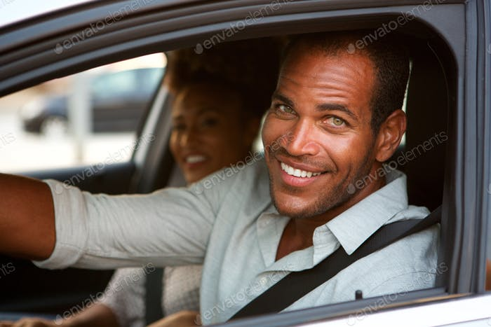 Close up of cheerful man and woman in car on road trip