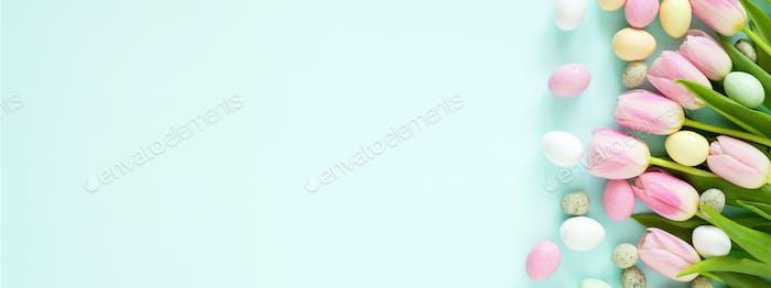 Banner mit Oster-farbigen Süßigkeiten-Eiern und Tulpen.