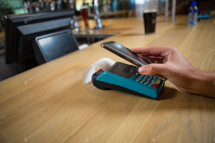 Cropped hand of customer making contactless payment