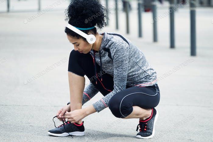 Fit und sportliche junge Frau binden ihre Schnürsenkel vor einem Lauf.