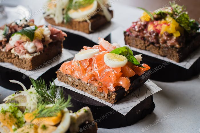 Scandinavian snack. Smorrebrod. Traditional Danish sanwiches, dark rye bread with different topping