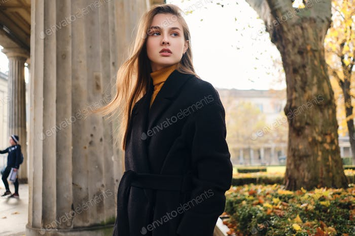 Gorgeous stylish girl in coat intently looking away in autumn park
