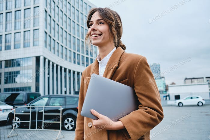 Young smiling lawyer in coat with laptop happily looking away walking through city street