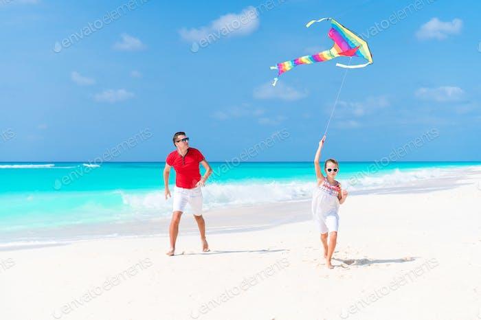 Glücklicher Vater und niedliche kleine Tochter fliegen Drachen zusammen am tropischen Strand