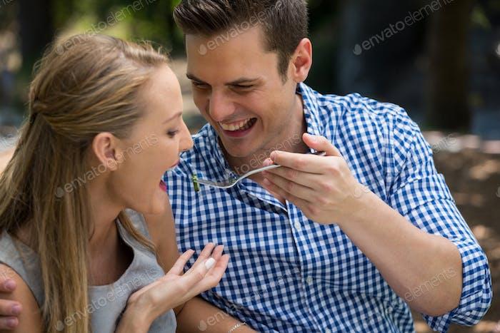 Smiling man feeding woman at outdoor restaurant
