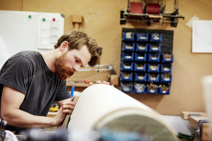 A man in furniture workshop working on a curved wooden piece of furniture.