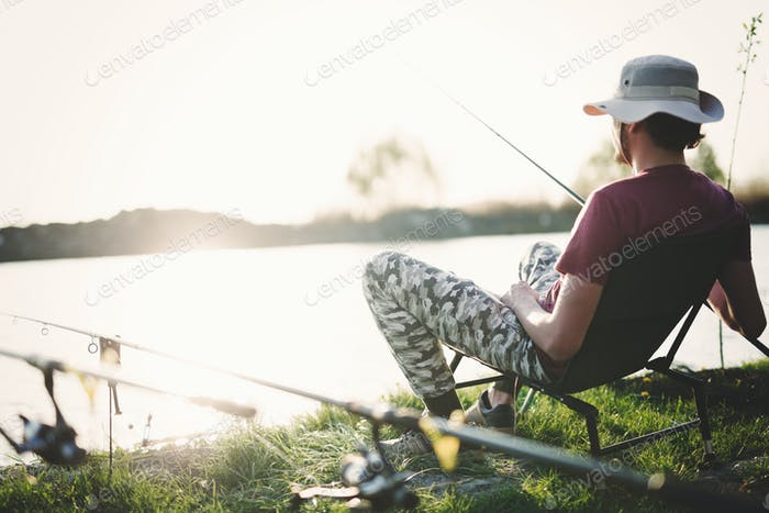 Young man fishing on lake at sunset enjoying hobby