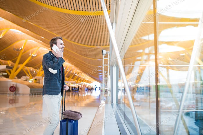 man using mobile phone at the airport looking trough the window