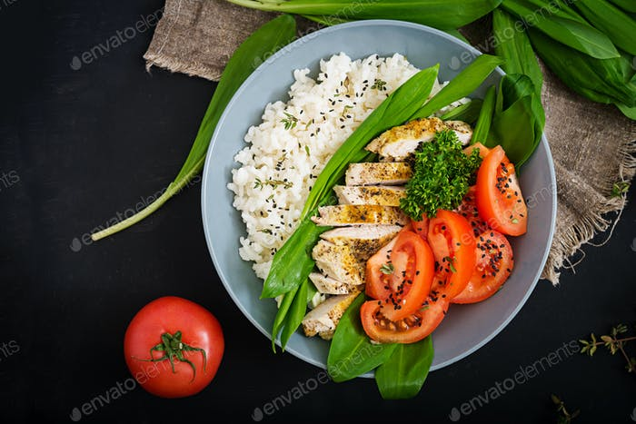 Healthy salad with chicken, tomatoes, wild garlic and rice