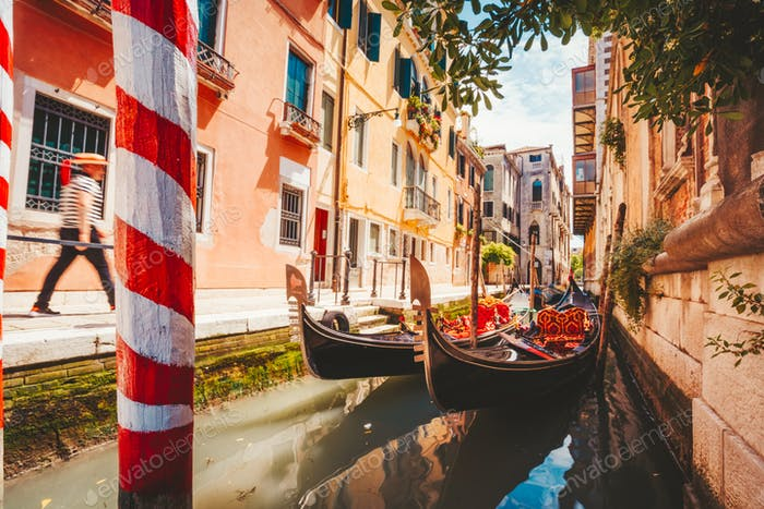 Gondolas boat floating in narrow canal of Venice city on beautiful sunny day. Italy. Europe