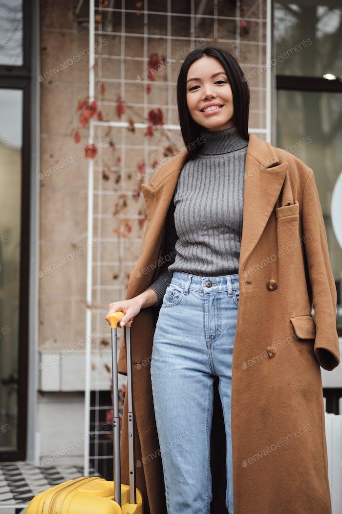 bastante elegante chica asiática en abrigo alegremente buscando en cámara con maleta en la calle