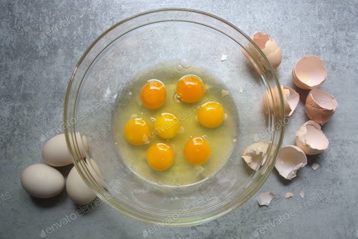 Raw eggs in glass bowl