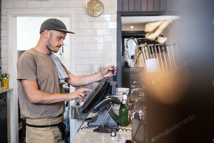 Bearded man wearing baseball cap standing at a till in a restaurant.