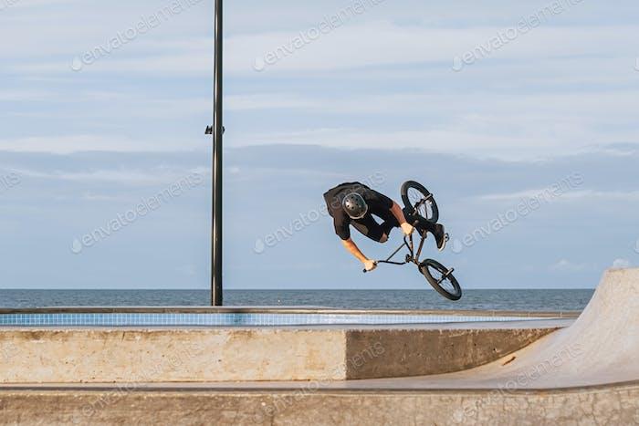 Bmx rider performing a jump on a skatepark