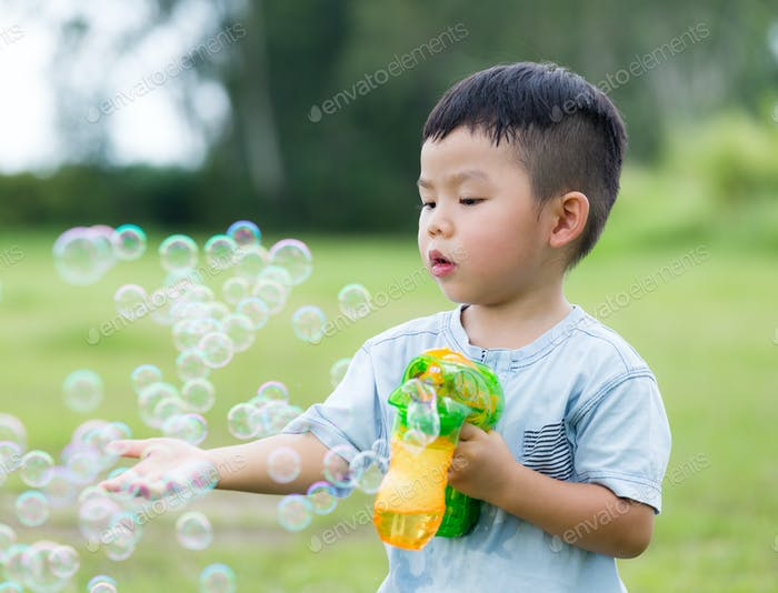 Young boy play with bubble gun and touch on the bubble