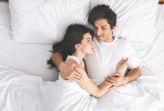 Young loving couple sleeping in bed and hugging
