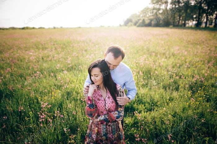 Heureuse famille élégante embrassant dans le champ vert