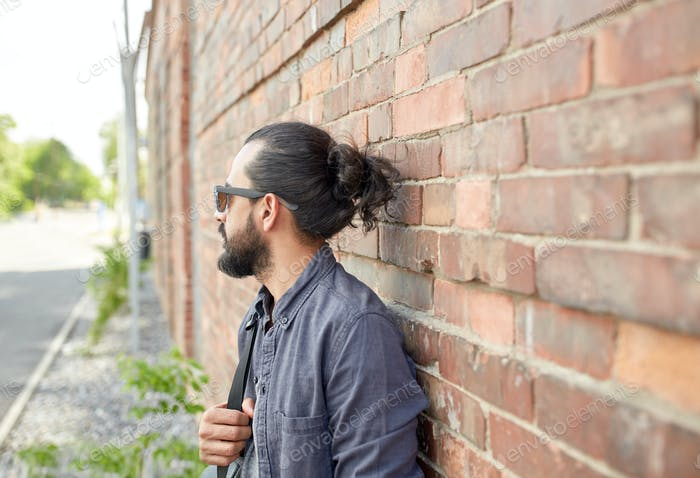man with backpack standing at city street wall