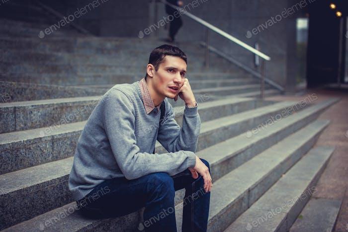 Toughtful man sitting on steps.