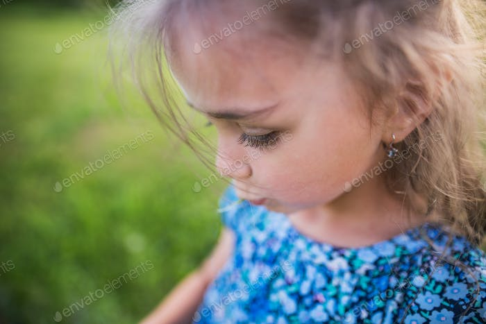 A small girl in the garden in spring nature. Copy space.