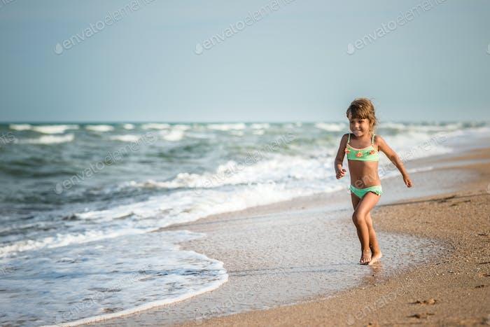 Joyful little girl enjoys a beach day