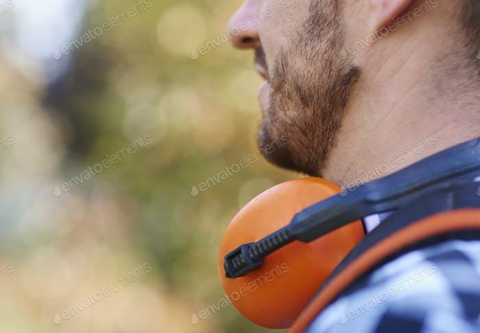 Part of gardener's face with headphones