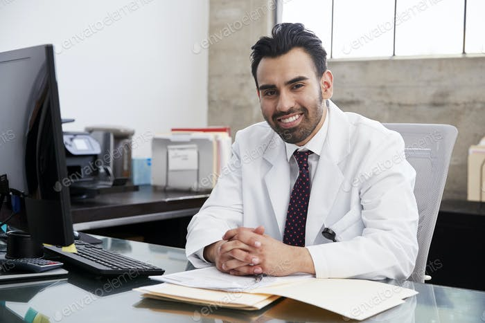 Smiling Hispanic male doctor sitting at desk, portrait