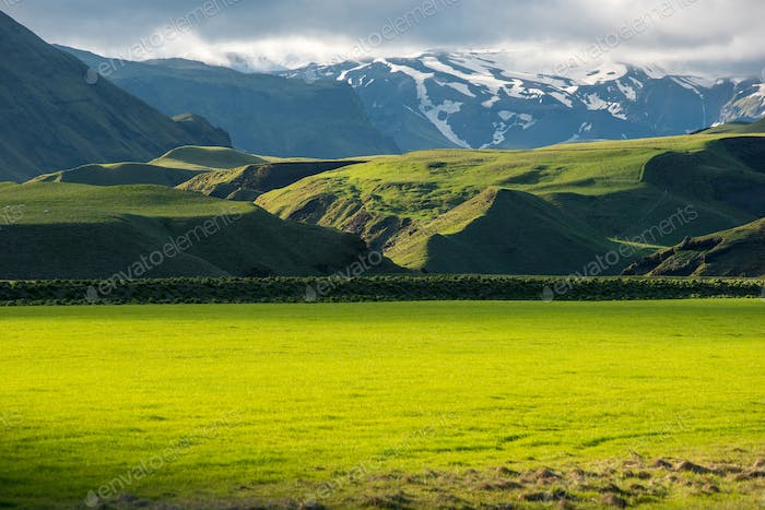 Wonderful Icelandic landscape, grassland in the highland mountains in late afternoon lights
