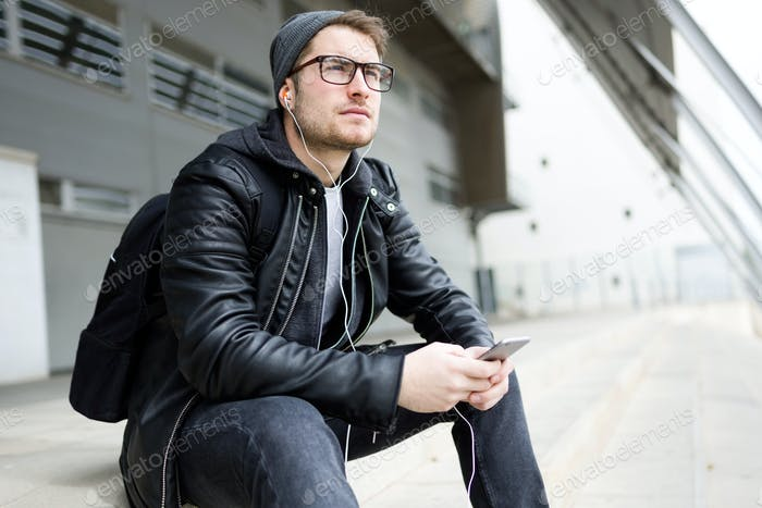 Modern young man listening to music with mobile phone in the str